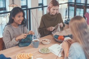 Girls sat around a table knitting