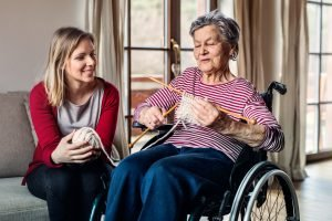 Young woman and older woman in wheelchair with knitting