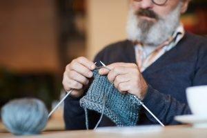 Older bearded man knitting